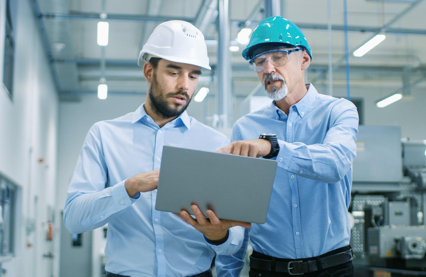 Instandhalter mit Laptop in Produktionshalle