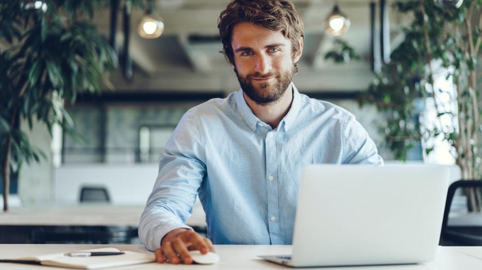 Mann schaut Webinar am Laptop