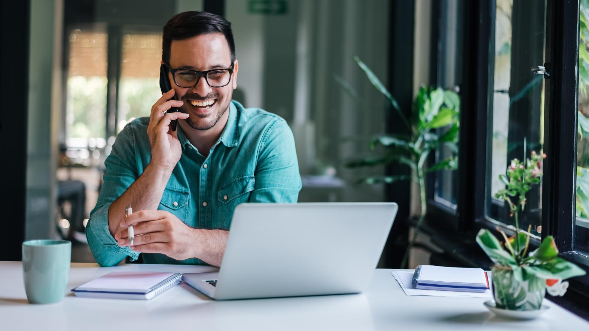 Mann telefoniert und sitzt am Laptop